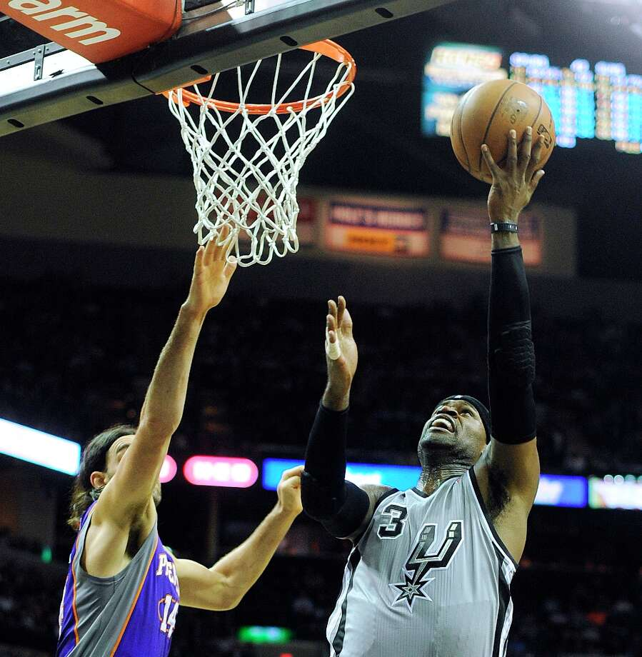 Stephen Jackson of the Spurs scores after being fouled as Luis Scola of the Phoenix Suns defends  at the AT&T Center on Saturday, Jan. 26, 2013. Jackson made the ensuing free throw. Photo: Billy Calzada, San Antonio Express-News / SAN ANTONIO EXPRESS-NEWS