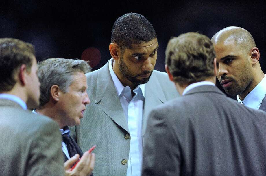 Tim Duncan (middle), a cornerstone of the Spurs, listens in on a coaches meeting during a timeout in action against the Phoenix Suns at the AT&T Center on Saturday, Jan. 26, 2013. Duncan is injured and currently unable to play. Photo: Billy Calzada, San Antonio Express-News / SAN ANTONIO EXPRESS-NEWS