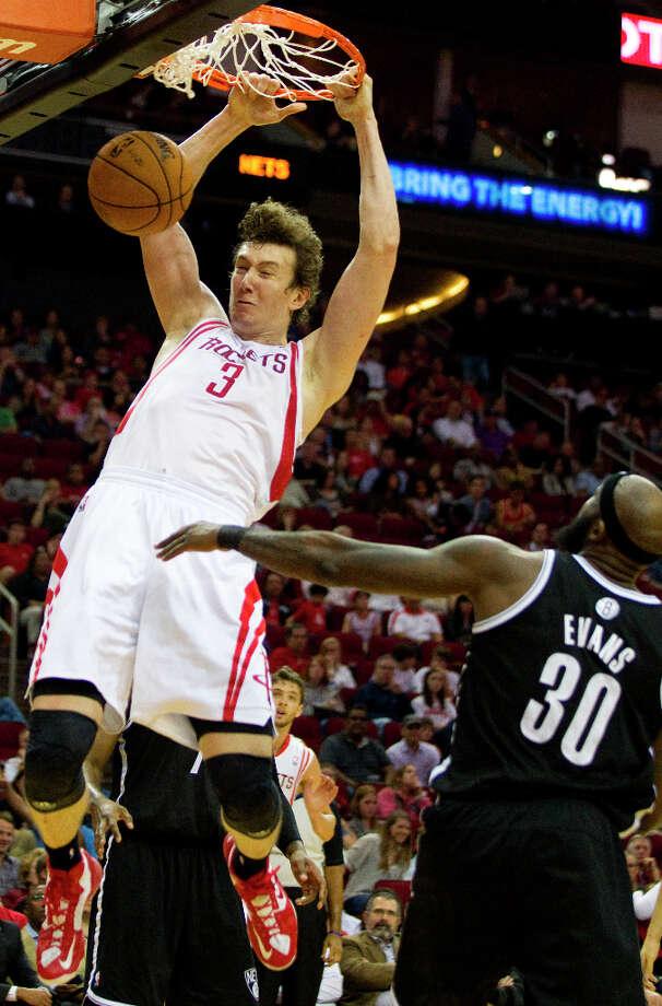 Rockets center Omer Asik (3) scores on a dunk over Nets power forward Reggie Evans. Photo: Brett Coomer, Chronicle / © 2013 Houston Chronicle