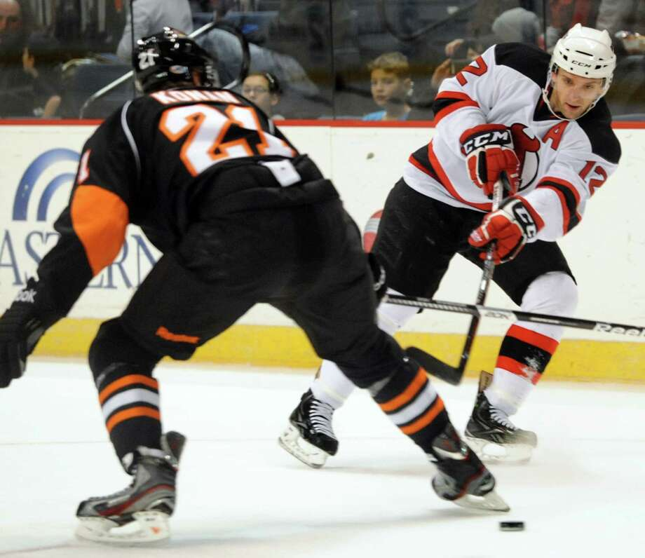 Devils' Tim Sestito (12), right, gets the puck past Phantoms' Matt Konan (21) during their hockey game against the Adirondack Phantoms on Saturday, Jan. 26, 2013, at Times Union Center in Albany, N.Y. Teammate Bobby Butler, not pictured, connected with the pass and scored in the first period. (Cindy Schultz / Times Union) Photo: Cindy Schultz / 00020855B