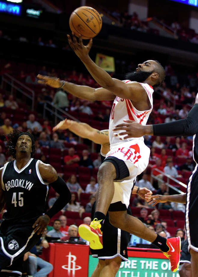 Rockets guard James Harden (13) leaps past Nets forward Gerald Wallace (45) for a layup. Photo: Brett Coomer, Chronicle / © 2013 Houston Chronicle