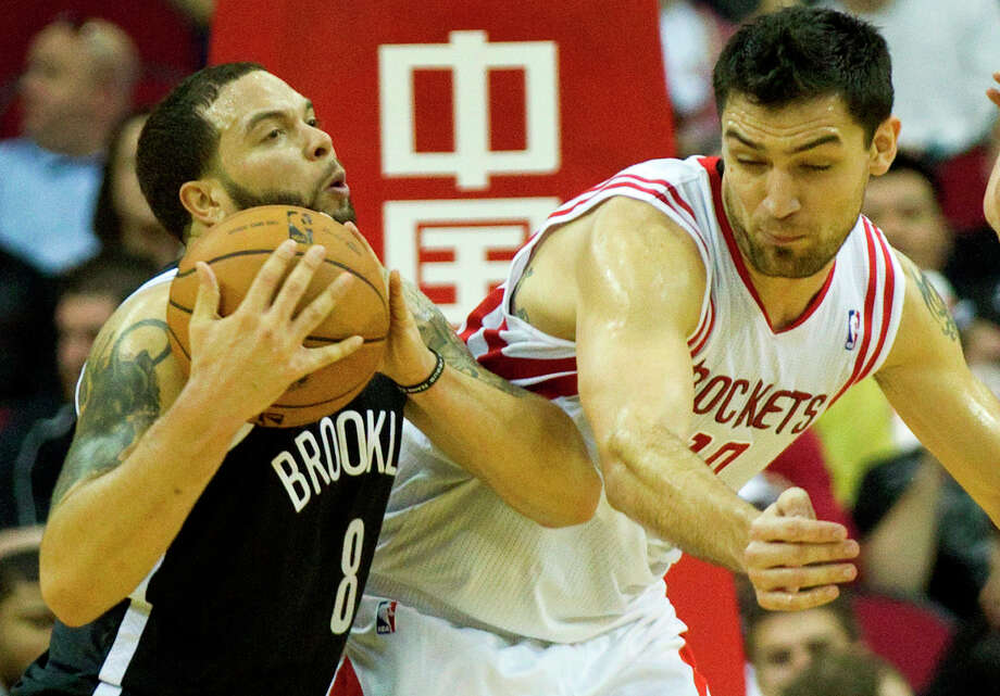Nets point guard Deron Williams (8) pulls the ball away from an attempted steal by Rockets forward Carlos Delfino. Photo: Brett Coomer, Chronicle / © 2013 Houston Chronicle