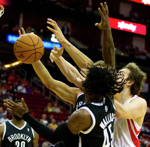 Nets forward Gerald Wallace (45), Nets center Brook Lopez, obscured, and Rockets center Omer Asik (3) battle for a rebound. Photo: Brett Coomer, Chronicle / © 2013 Houston Chronicle