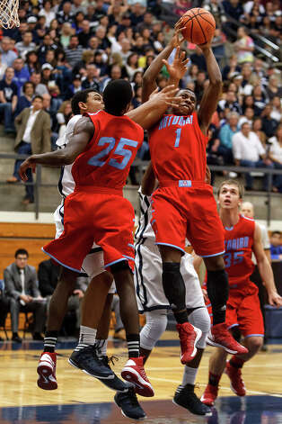 Antonian's Sterling Holmes (1) and Tobe Akabogu (25) battle with Central Catholic's Antoine Carr for a rebound during the first half of their game at Paul Taylor Field House on Jan. 26, 2013.  Central Catholic beat the Apaches 64-53.  MARVIN PFEIFFER/ mpfeiffer@express-news.net Photo: MARVIN PFEIFFER, Express-News / Express-News 2013