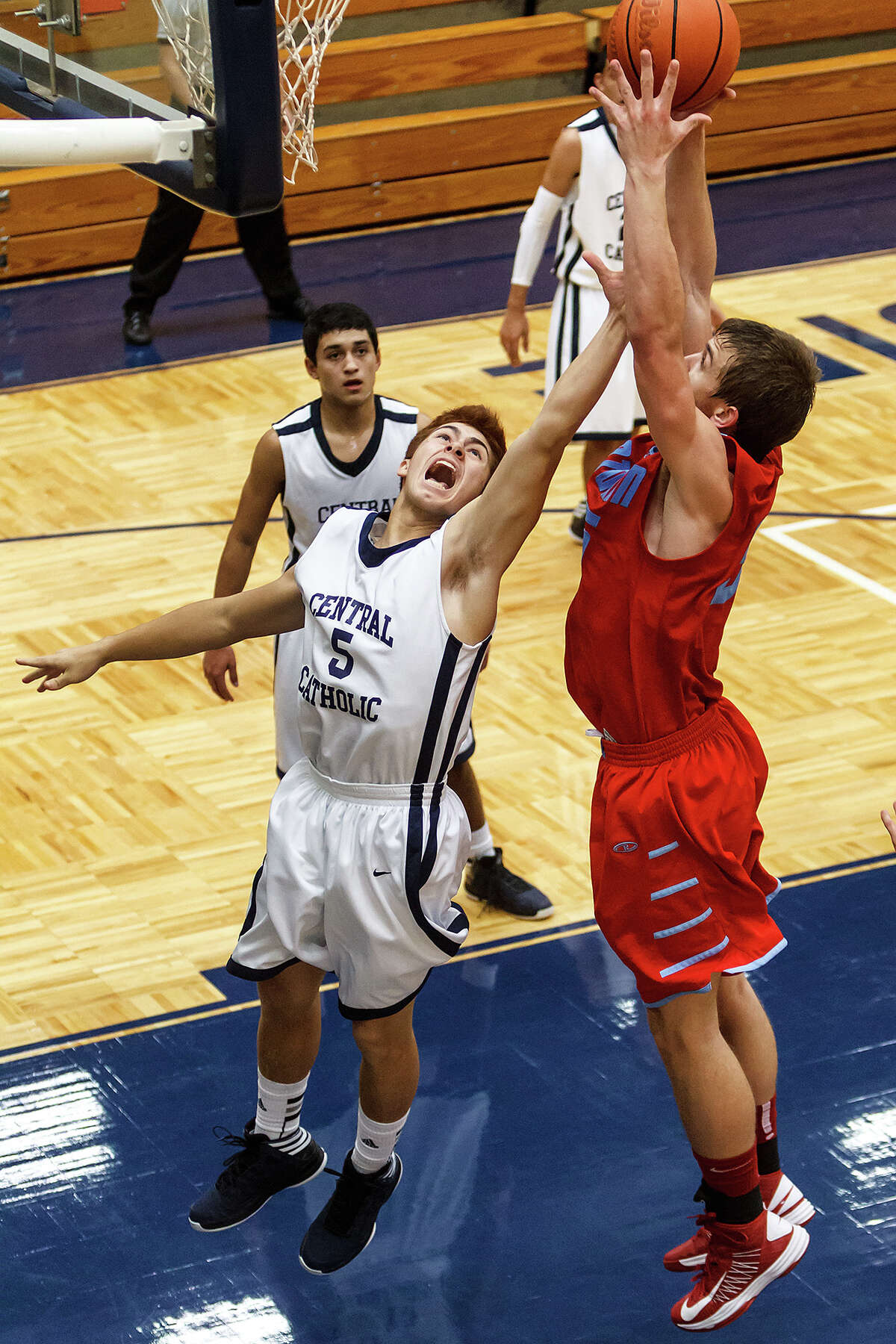 Central Catholic's Joseph Nava (left) fights with Antonian's Reagan Keogh during the second half of their game at Paul Taylor Field House on Jan. 26, 2013. Central Catholic beat the Apaches 64-53. MARVIN PFEIFFER/ mpfeiffer@express-news.net