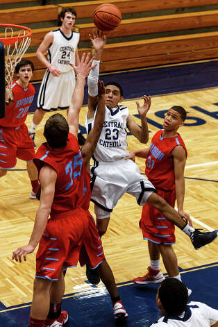 Central Catholic's Chris Paz (center) puts up a shot over Antonian's Reagan Keogh (left) and Doug Bradshaw during the first half of their game at Paul Taylor Field House on Jan. 26, 2013.  Central Catholic beat the Apaches 64-53.  MARVIN PFEIFFER/ mpfeiffer@express-news.net Photo: MARVIN PFEIFFER, Express-News / Express-News 2013