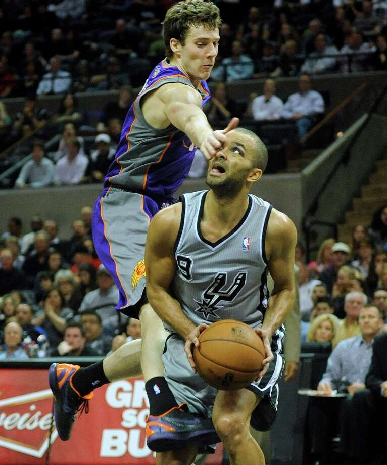 Tony Parker of the Spurs is slapped on the eye by Goran Dragic of the Phoenix Suns as he goes up for a shot late in the game at the AT&T Center on Saturday, Jan. 26, 2013. Parker made the shot. No foul was called. Photo: Billy Calzada, San Antonio Express-News / SAN ANTONIO EXPRESS-NEWS