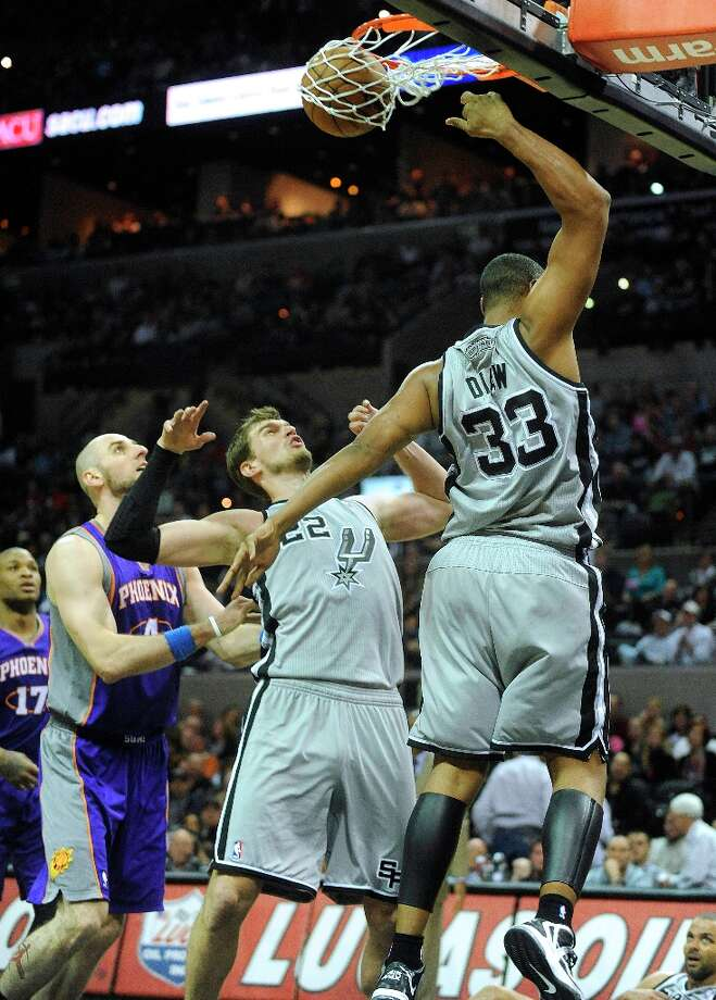 Boris Diaw of the Spurs dunks as teammate Tiago Splitter and the Phoenix Suns' Marcin Gortat (4) and P.J. Tucker watch late in the game at the AT&T Center on Saturday, Jan. 26, 2013. Photo: Billy Calzada, San Antonio Express-News / SAN ANTONIO EXPRESS-NEWS
