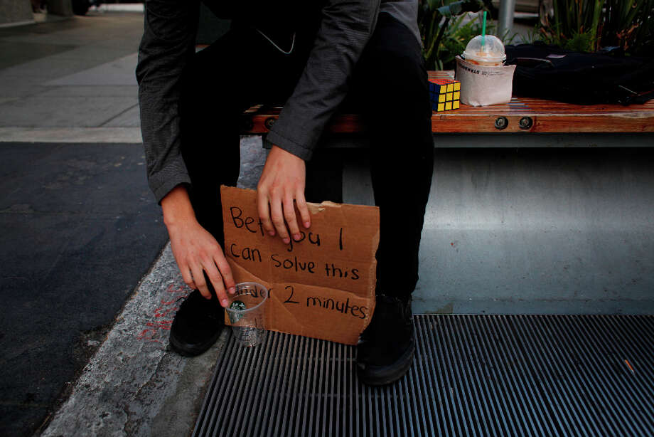 Francisco Perez, 18, adjusts his cardboard sign that challenges people that he can solves  his the Rubik's Cube in less that two minutes on Powell Street in San Francisco. Photo: Mike Kepka, The Chronicle / ONLINE_YES