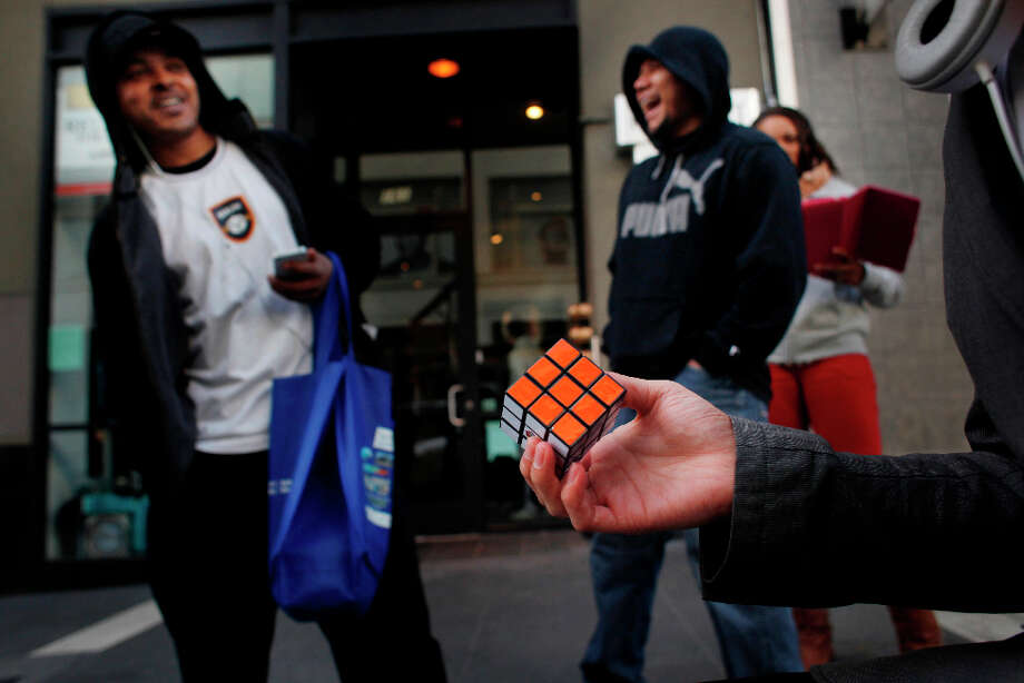Francisco Perez, 18, shoes off a completed Rubik's Cube to an invested person on Powell Street. The feet prompted a one dollar tip. Photo: Mike Kepka, The Chronicle / ONLINE_YES