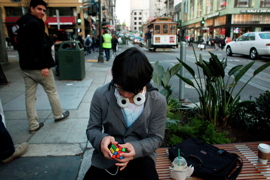 Waiting his next two minute challenge, Francisco Perez, 18, quietly twists his Rubik's Cube on Powell Street in San Francisco. Photo: Mike Kepka, The Chronicle / ONLINE_YES