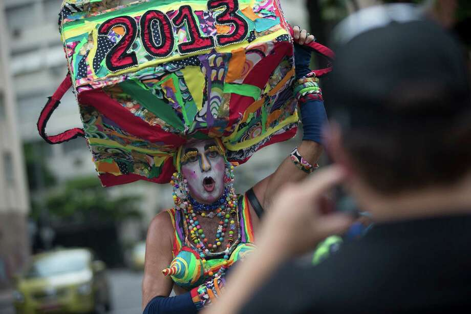 Eduardo Rasberge, 48, known as Suitcase Woman wears a decorative suitcase on his head while posing for a photo during the Banda de Ipanema block parade, a pre-Carnival event, in Rio de Janeiro, Brazil, Saturday, Jan. 26, 2013.  The Suitcase Woman has been a Carnival regular for the past 30 years, honoring women and inspired by singer Carmen Miranda. According to Rio's tourism office, Rio's street Carnival this year will consist of 492 block parties, attended by an estimated five million Carnival enthusiasts. (AP Photo/Silvia Izquierdo) Photo: Silvia Izquierdo