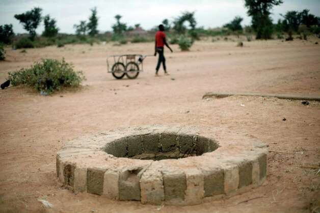 A man pulls a cart past a well on Friday where several bodies were dumped in Sevare north of Mali's capital, Bamako. A witness told The Associated Press that he saw soldiers fatally shoot at least three people at a nearby bus stop and dump their bodies in the well. Mali's government is warning soldiers to respect human rights following reports of the civilians being killed. Photo: AP