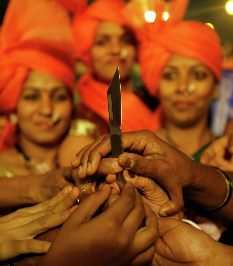 Women reach out their hands to collect knives being distributed by local leaders of Shiv Sena, a right-wing party in Mumbai, India, Wednesday. According to local news reports, the local leaders of the party distributed the knives to women for their self -defense at an event held to mark the birth anniversary of the party founder Bal Thackeray who died recently. Photo: AP