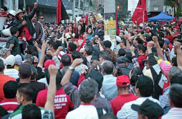"Rasel Tome,  coordinator of the Progressive Resistance Movement and member of the opposition Libre party talks to supporters against recent laws approved by congress outside parliament in Tegucigalpa, Honduras, Thursday.  Honduras has been on the brink of bankruptcy for months, as lawmakers put off passing a government budget necessary to pay for basic government services. The country is also grappling with $5 billion in foreign debt, the biggest hole in its history and equivalent to last year's entire government budget. The sign reads in Spanish '""The nation is not for sale, you honor it and you defend it. Congressmen with no country, go to a different dog with that bone."" Photo: AP"