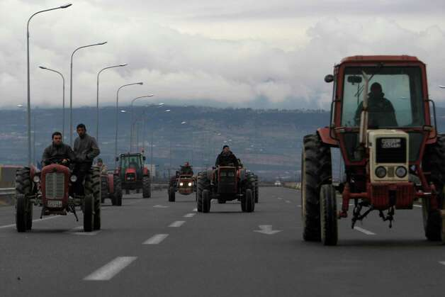 "Farmers drive their tractors on Egnatia highway near the northern Greek city of Veria, Greece, on Saturday. Farmers from Veria used their tractors to block Greece's northern highway ""Egnatia"" for about an hour. Some farmers are complaining they have not yet received state subsidies while others say compensation for natural disasters that have hurt their crops is too low. Photo: AP"
