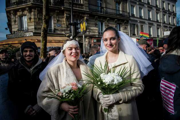 Women pose during a demonstration for the government project to legalize same-sex marriage and adoption for same-sex couples in Paris, France, Sunday. Photo: AP