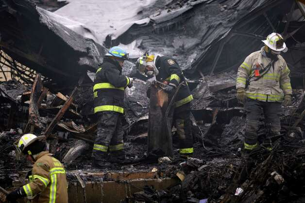 Investigators look over the aftermath of a fire at the Melrose Shopping Center Friday in Cheltenham, Pa. The fire at a shopping center in suburban Philadelphia has damaged nearly a half dozen stores and left one person dead.  Officials say police pulled one person from the blaze and that the victim later died at a hospital. Two firefighters also suffered minor injuries. Photo: AP