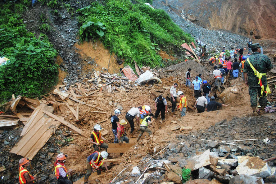 Workers clear landslide debris in the mining town of Pueblo Nuevo, Ecuador, Thursday. At least six p