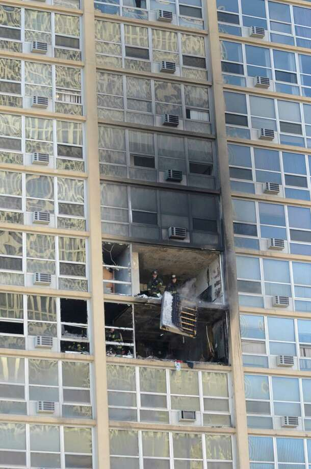 Chicago firefighters are seen inside an apartment in a high-rise building after a blaze that started on the seventh floor of the building in the city's South Shore neighborhood Tuesday. The fire injured three people who were taken to area hospitals. (AP Photo/Chicago Sun-Times, Brian Jackson) Photo: AP