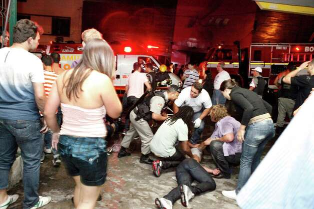 People help an injured man, victim of a fire in a club in Santa Maria city, Rio Grande do Sul state,  Brazil,  on Sunday.  According to police more than 200 died in the devastating nightclub fire in southern Brazil.  Officials say the fire broke out at the Kiss club in the city of Santa Maria while a band was performing. At least 200 people were also injured. Photo: AP