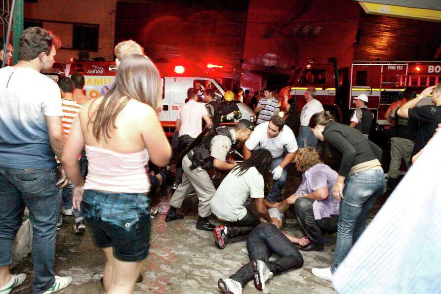 People help an injured man, victim of a fire in a club in Santa Maria city, Rio Grande do Sul state,