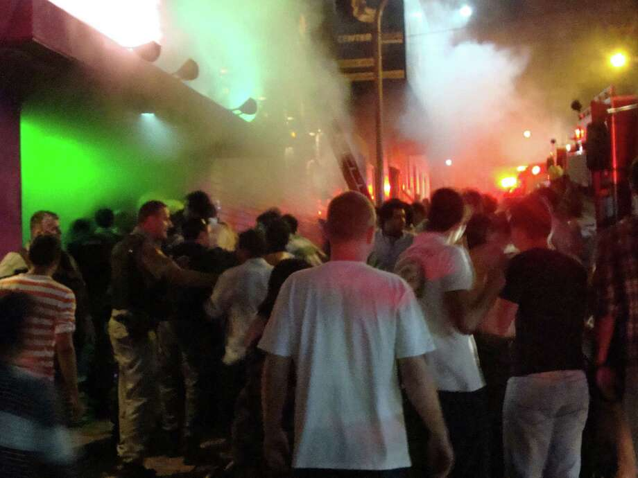 A crowd stands outside the Kiss nightclub during a fire inside the club in Santa Maria city,  Rio Grande do Sul state, Brazil, on Sunday.  A blaze raced through the crowded nightclub in southern Brazil early Sunday, killing 245 people as the air filled with deadly smoke and panicked party-goers stampeded toward the exits, police and witnesses said. It appeared to be the world's deadliest nightclub fire in more than a decade. Photo: AP
