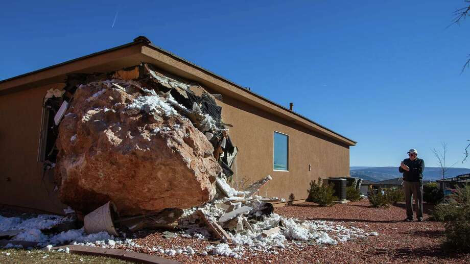 A bystander photographs a 12-by-9-foot boulder as it rests in the master bedroom of a home in St. George, Utah on last Saturday.  Wanda Denhalter, 63, was sleeping alone when she narrowly missed being crushed under the boulder early Saturday morning, said her husband, Scot Denhalter.  She was taken to a St. George hospital, where she underwent four hours of surgery for non-life-threatening injuries. She also suffered a large leg gash.  It's unknown what caused the boulder to come down about 3 a.m., but Scot Denhalter thinks a broken water pipe at a ridgetop home might have had something to do with it. Photo: AP