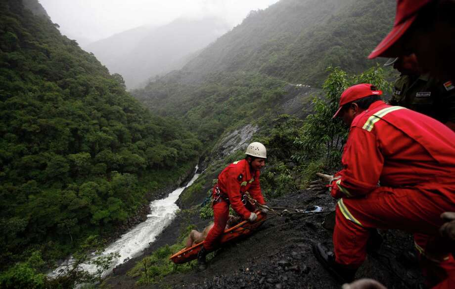 Rescue workers recover the body of a victim after a bus crash on the outskirts of Pijchu, Bolivia, Monday. According to police, at least ten people were killed and several injured after a bus drove off a mountain road and plunged down a ravine early Monday Photo: AP