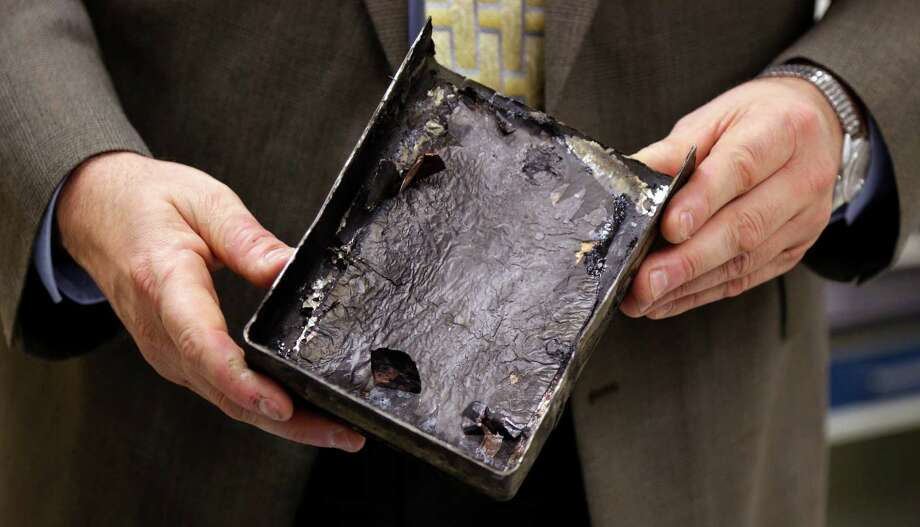 "National Transportation Safety Board's Joseph Kolly, holds an fire-damaged battery casing from the Japan Airlines Boeing 787 Dreamliner that caught fire at Logan International Airport in Boston, at the NTSB laboratory in Washington, Thursday. The battery that caught fire in Boston shows evidence of short-circuiting and a chemical reaction known as ""thermal runaway,"" in which an increase in temperature causes progressively hotter temperatures, federal accident investigators said. However, it's not clear to investigators which came first, the short-circuiting or the thermal runaway. Photo: AP"