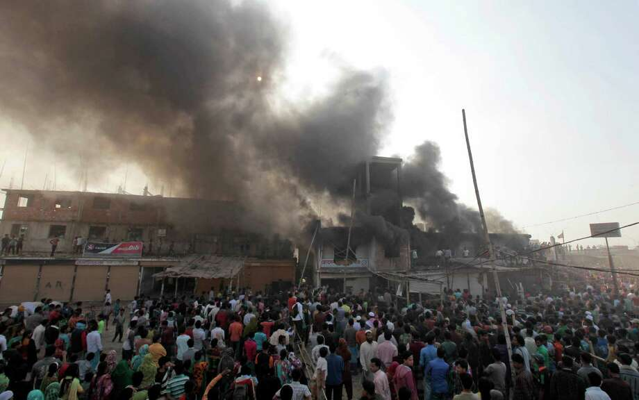 Smoke rises from a two-storied garment factory after a fire swept through it in Dhaka, Bangladesh, Saturday. The fire swept killed at least six female workers and injured another five, police and fire officials said. The latest fire occurred more than two months after a deadly fire killed 112 workers in another factory near the capital city, raising questions about the safety measures in Bangladesh garment industry. Photo: AP