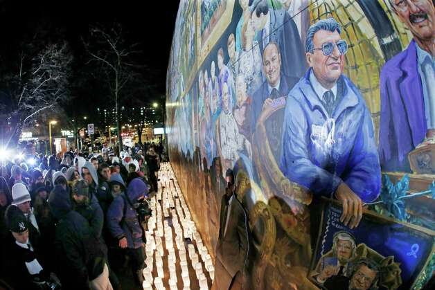 People gather in front of a mural containing a likeness of former Penn State football coach Joe Paterno, right, at a candlelight memorial on the first anniversary of his death, Tuesday in State College, Pa. Photo: AP