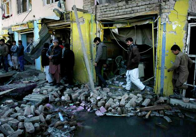 Afghans walk over debris outside the Kabul traffic police headquarters building, unseen, which was attacked by militants in Kabul, Afghanistan, Monday. Police say a Taliban raid of the Kabul traffic police headquarters is over and that three police officers and at least five insurgents have been killed in the hours-long fighting. Photo: AP