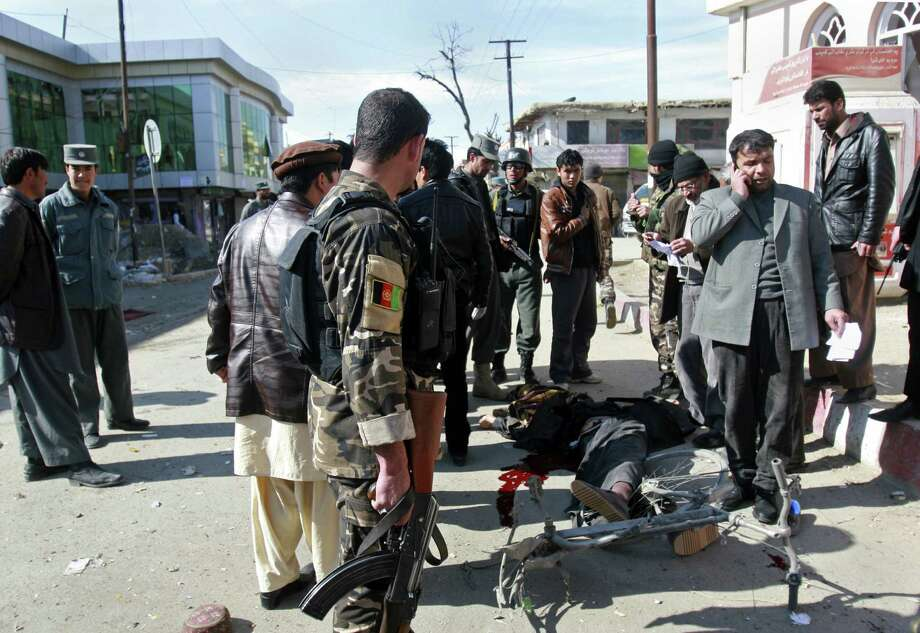 Security officers investigate the scene of a bomb in Gazni, Afghanistan, Saturday. A remote controlled bomb planted on a bicycle killed several people including a police officer and a civilian in the eastern city of Ghazni and Gen. Zirawer Zahid, the provincial police chief, says another five people were wounded. Photo: AP