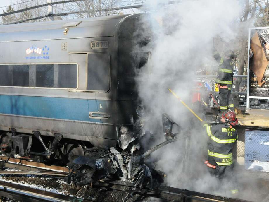 A car smolders after it was struck by an out-of-service Long Island Rail Road passenger train at the Brentwood station Suffolk Avenue crossing on Tuesday in New York. Officials said the gates were down when the train struck the car. Photo: AP