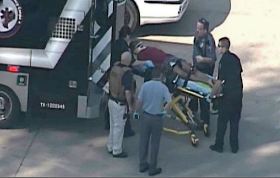 In this frame grab provided by KPRC Houston, an unidentified person is transported by emergency personnel at Lone Star College Tuesday in Houston. Two people have been charged in the shooting that left four people injured, three from gunshot wounds.  (AP Photo/Courtesy KPRC TV) Photo: AP