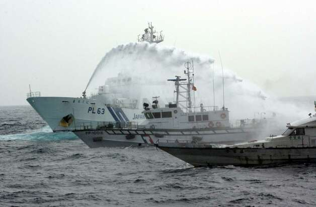 In this photo released by the Taiwan Coast Guard, a Japanese Coast Guard patrol boat, left, sprays a water cannon over a Taiwan Coast Guard boat to warn a Taiwanese leisure boat, right, carrying four Taiwanese activists that they not to go any further, near Tiaoyutai, in the East China Sea, Thursday. The activists attempted to sail to disputed islands known as Uotsuri in Japanese and Diaoyu Dao in Chinese, the biggest island in the disputed Senkaku or Diaoyu islands in East China Sea but were turned away by Japan's Coast Guard. Photo: AP