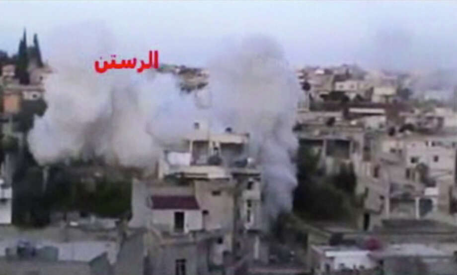 In this image taken from video obtained from the Ugarit News, which has been authenticated based on its contents and other AP reporting, smoke rises from buildings after rockets slammed into them in the rebel-held town of Rastan, Syria, just north of Homs on Friday. Regime troops shelled the city of Homs on Friday as soldiers battled rebels around the central province with the same name, which was a major frontline during the first year of the revolt. Photo: AP