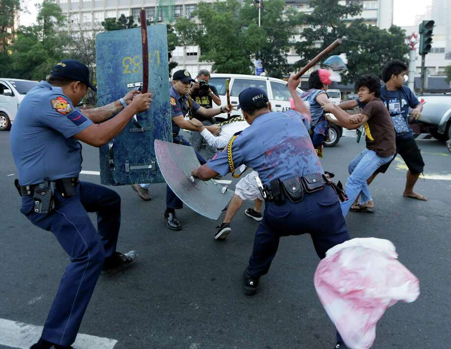 Police hit protesters after the latter managed to throw paint at the seal of the U.S. Embassy in Manila to protest the alleged destruction of the coral reef by the USS Guardian, a US minesweeper, which ran aground off Tubbataha Reef, a World Heritage Site, southwest of the Philippines early Friday. A U.S. Navy official said the USS Guardian has been punctured and taking in water and has to be lifted off the rocks. Photo: AP