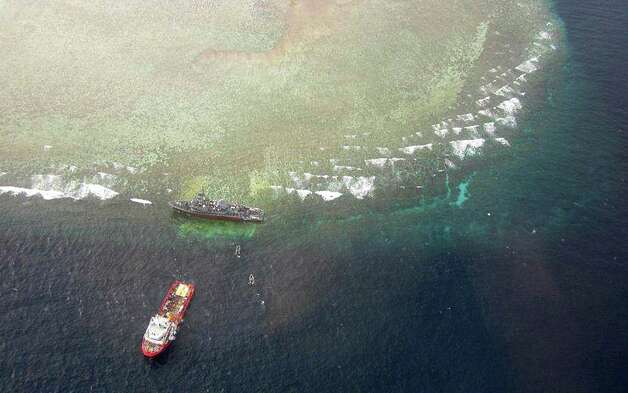 This photo, released by the Tubbataha Management Office, shows an aerial view of the U.S. Navy minesweeper USS Guardian, top, stranded in the Tubbataha Reef, a World Heritage Site in the Sulu Sea, 400 miles southwest of Manila, Philippines, Friday. A U.S. Navy official said the ship, which damaged about an estimated 1,000 square meters of its corals, has been punctured and taking in water and has to be lifted off the rocks. (AP Photo/Tubbataha Management Office)  Photo: AP