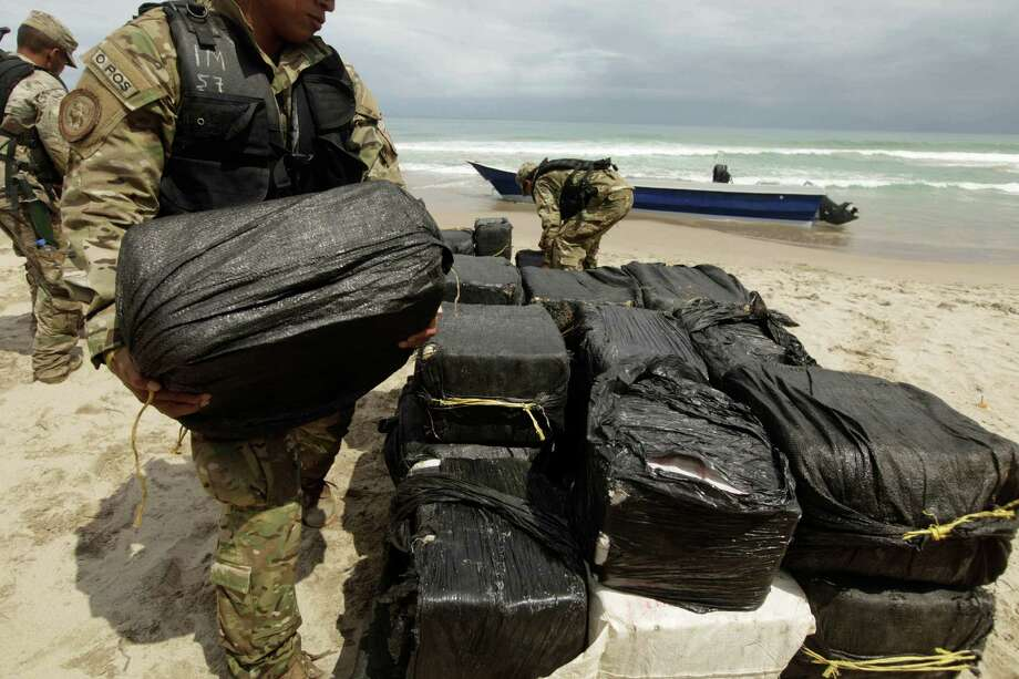 An air-naval police officer carries seized cocaine during a media tour organized by the Air-Navy on a beach near Rio Cana north-west from Panama City, Tuesday. According to Panama's air-naval police at the site, sacks containing a total of about one ton of cocaine were seized Monday night during a sea pursuit operation behind three alleged drug traffickers who escaped after capsizing their boat on the beach and running into a forest area. Photo: AP