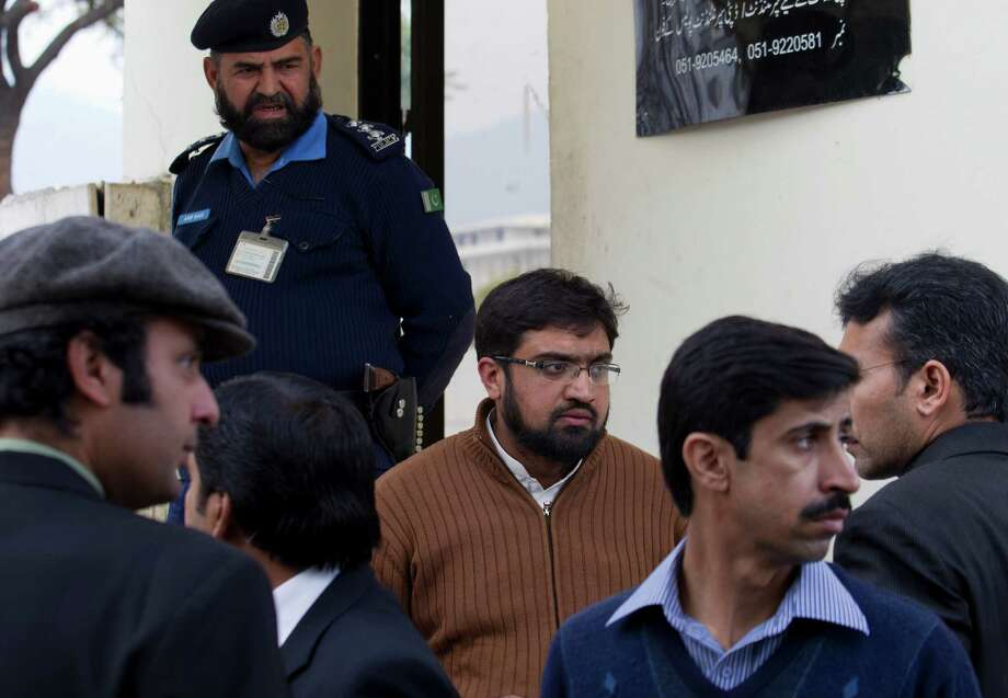 Hamid Munir, center, the brother-in-law of Pakistani officer Kamran Faisal, waits with Faisal's colleagues at the Supreme Court to submit an application regarding the death of Faisal in Islamabad, Pakistan, Wednesday. Officer Faisal was investigating a corruption case against the prime minister and was found dead in what police are calling a likely act of suicide. Faisal's death came days after the Supreme Court ordered the arrest of Prime Minister Raja Pervaiz Ashraf and 15 others in connection with an old corruption case that the officer was investigating. Photo: AP