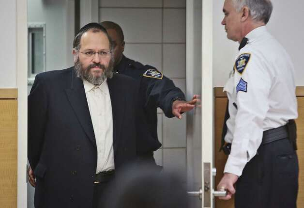 Nechemya Weberman, left, a religious counselor in New York City's ultra-orthodox Jewish community, is lead to court Tuesday in New York. Weberman was sentenced Tuesday to 103 years in prison for molesting a girl who came to him with questions about her faith. He was convicted in December of 59 counts, including sustained sexual abuse of a child, endangering the welfare of a child and sexual abuse. Photo: AP