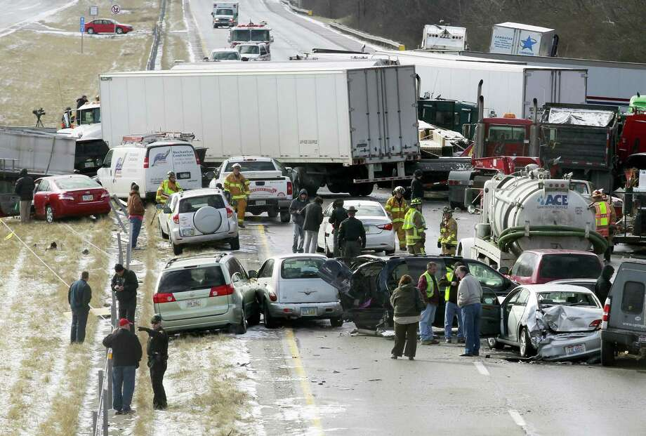 Semi-trucks and other vehicles involved in a mulit-car crash are strewn across westbound Interstate 275 between Colerain Avenue and Hamilton Avenue on Monday in Cincinnati. The accident left about 20 people injured. There have been three separate highway pileups involving dozens of vehicles in Ohio. Authorities say as many as 50 vehicles could be involved in a pileup on Interstate 75 in southwest Ohio.  (AP Photo/Cincinatti Enquirer, Cara Owsley) Photo: AP