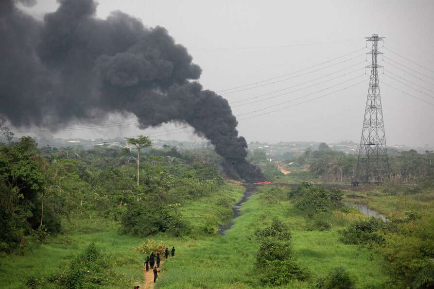 Nigerian civil defense corps officials secure the area following an explosion at a gasoline pipeline