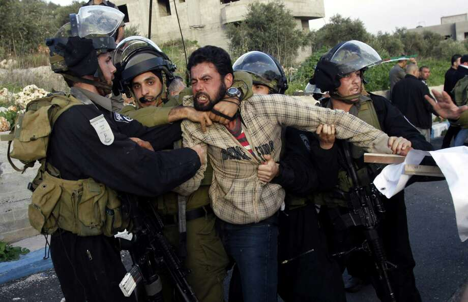 Israeli security forces detain a Palestinian during clashes in the West Bank village of Anin, on Saturday. Hundreds of Palestinians clashed with Israeli security during a rally in support of Palestinians in Israeli jails. Photo: AP