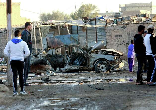 People gather at the scene of a car bomb attack in Shula neighborhood, Baghdad, Iraq, on Tuesday. A string of car bomb attacks in and around Baghdad, killing and wounding scores of people, police said, deepening fears of an increase in violence as sectarian tensions simmer in Iraq. Photo: AP