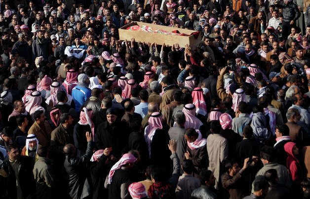 Mourners chant slogans against Iraq's Shiite-led government as they carry the coffin of a slain protester during a mass funeral in Fallujah, 40 miles west of Baghdad, Iraq, Saturday. Hundreds of Iraqi protesters have gathered in a western city for the funeral of six protesters killed during shooting by army troops a day earlier. Photo: AP