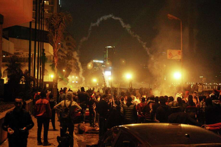 Demonstrators throw stones on Saturday at security forces who respond with tear gas in front of international hotels along the Nile in downtown Cairo, Egypt. Unrest surrounding the second anniversary of Egypt's revolution broke out in Cairo and other cities for a third day, with protesters clashing for hours with riot police who fired tear gas that encompassed swaths of the capital's downtown. Photo: AP
