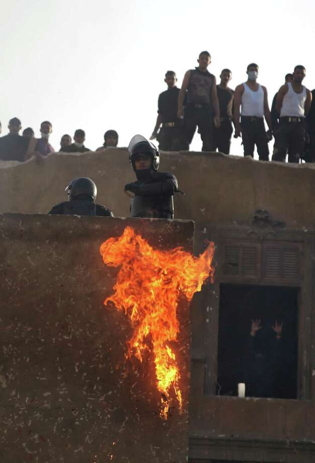 Egyptian riot police takes a position on a building overlooking demonstrators as a firebomb explodes during clashes with protesters, not seen, near Tahrir Square, Cairo, Egypt, on Saturday. The latest bout of violence in Egypt has left at least 38 people dead in two days of protests in cities across Egypt. Photo: AP